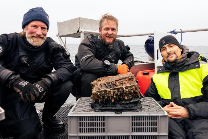 Les plongeurs et les archéologues posent avec une machine Enigma qu'ils ont trouvée dans les eaux de la baie de Gelting (Allemagne), le 11 novembre.