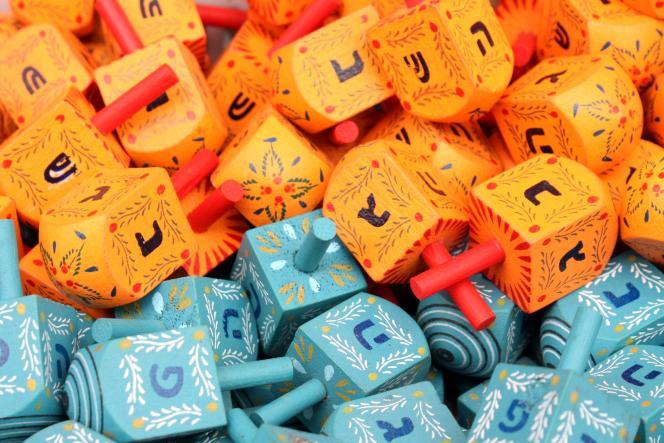 Deux versions de sevivonim (toupies de Hanouka) sur un étal au marché : ceux utilisés en Israël (lettres נגהפ), en bleu, et ceux à destination de la diaspora (lettres נגהש), en orange.