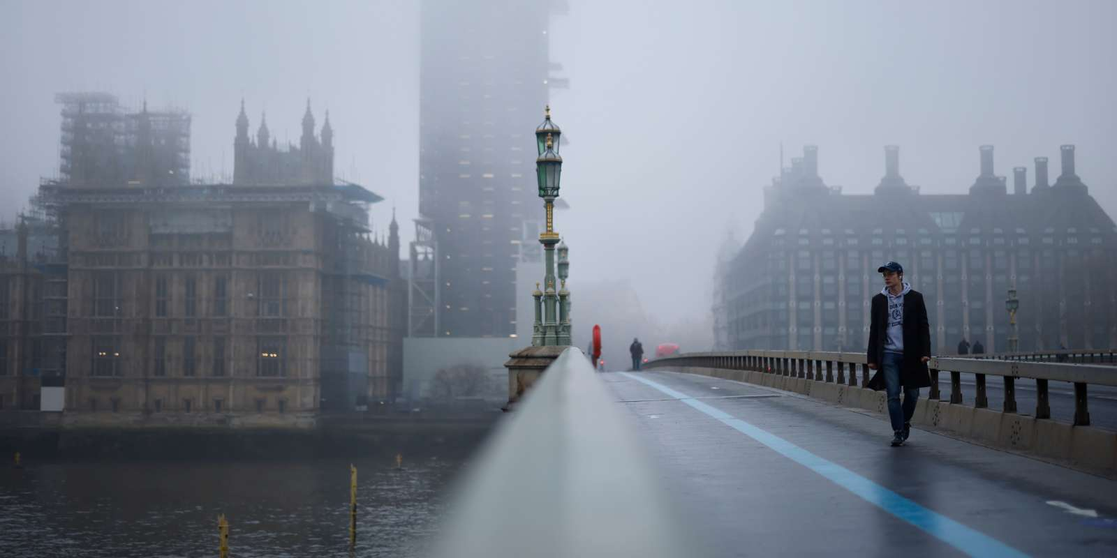 TOPSHOT - Pedestrians cross Westminster Bridge as fog envelopes the Elizabeth Tower, commonly known by the name of the bell,