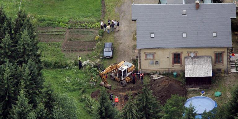 Les fouilles pour retrouver les dépouilles de deux des victimes du présumé tueur en série Michel Fourniret ont commencé suivant les indications de ce dernier et de son épouse le 03 juillet 2004 au domaine du château du Sautou. Les travaux d'excavation au château de Sautou (Ardennes) se poursuivaient samedi après-midi dans les deux zones désignées par le tueur en série présumé Michel Fourniret qui a affirmé y avoir enterré deux de ses victimes, a-t-on appris auprès des gendarmes. Une pelleteuse a commencé à creuser une zone située derrière le château, alors qu'un autre engin continuait son travail entamé dans la matinée, le long d'un chemin devant la bâtisse, a précisé à l'AFP un gendarme qui a requis l'anonymat.   Police search for bodies at the Chateau de Sautou in Donchery, northeastern France, 03 July 2004. Michel Fourniret, 62, who has admitted to killing nine people, eight of them young women and girls, was brought to the site with his wife, Monique Olivier. During the first day's search at the chateau Fourniret once owned in the wooded Ardennes region near the Belgian border, police found the bodies of Belgian girl Elysabeth Brichet, 12, and French student Jeanne-Marie Desramault, 22. (Photo by FRANCOIS NASCIMBENI / AFP)