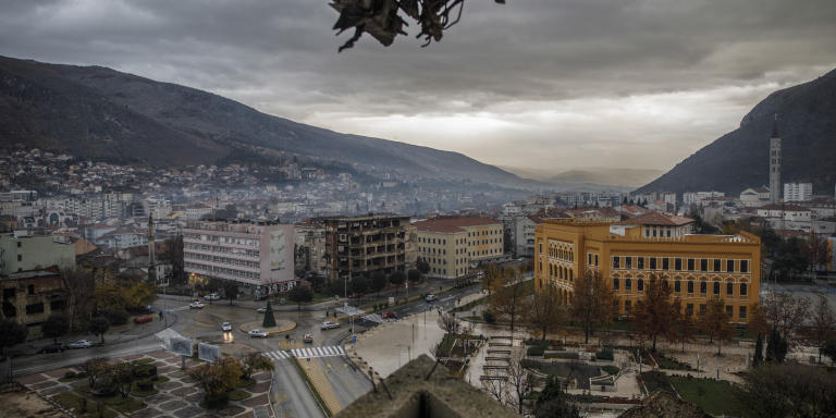 A view from the so-called Sniper Tower, a destroyed building of a former bank overlooking the square and the boulevard that were a front line during the country's 1992-95 war and where several important institutions are now placed, including the City Council, in Mostar December 5, 2020. Photo by Damir Sagolj for Le Monde  Janja Marusic:  Le bâtiment du conseil municipal de Mostar, au croisement des anciennes lignes de front.  « Je veux prendre la suite de mon père au conseil municipal. Grâce à nous [les Croates], Mostar deviendra une ville européenne moderne. »