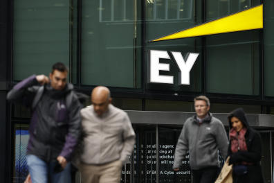 Pedestrians walk past the offices of accounting and auditing firm EY, formerly Ernst & Young, in London on November 20, 2020. - Britain's audit sector, dominated by the so-called Big Four accountancy giants, is shortly expected to discover how it must reinvent itself amid a series of probes into alleged corruption, including one linked to the collapse of German electronic payments group Wirecard. The Department for Business, Energy and Industrial Strategy (BEIS) is reportedly set to publish reform proposals before Christmas amid fraudulent probes into EY-linked activities at Denmark's Danske Bank and Wirecard. EY has been accused of failing to warn about suspicious transactions at Danish bank Danske Bank worth billions of euros. (Photo by TOLGA AKMEN / AFP)