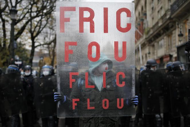 Un manifestant portant une pancarte lors de la manifestation contre le projet de loi sur la sécurité globale et le projet de loi «séparatisme», samedi 12 décembre à Paris.