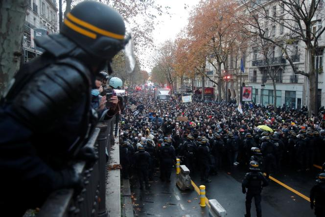 Des CRS se tiennent devant la marche contre la loi « sécurité globale», à Paris, le 12 décembre.