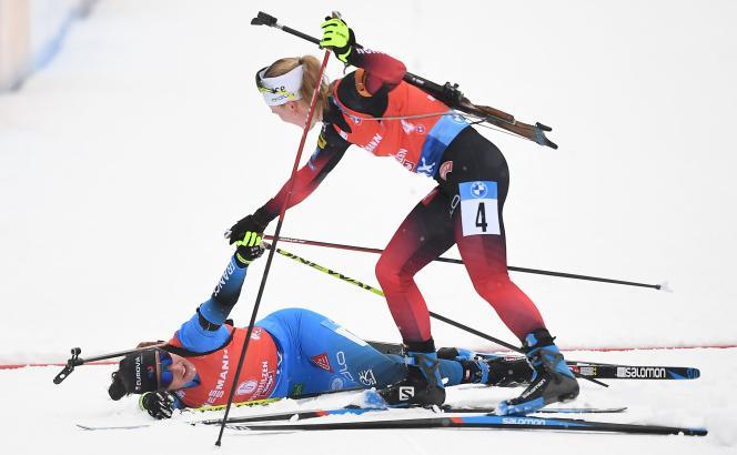 Marte Olsbu Roeiseland félicite et relève Julia Simon à l'issue de la course.