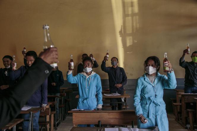 Des élèves brandissent des bouteilles de Covid Organics, une boisson promue par le gouvernement malgache comme remède au coronavirus, dans un lycée d'Antananarivo, le 23avril 2020.