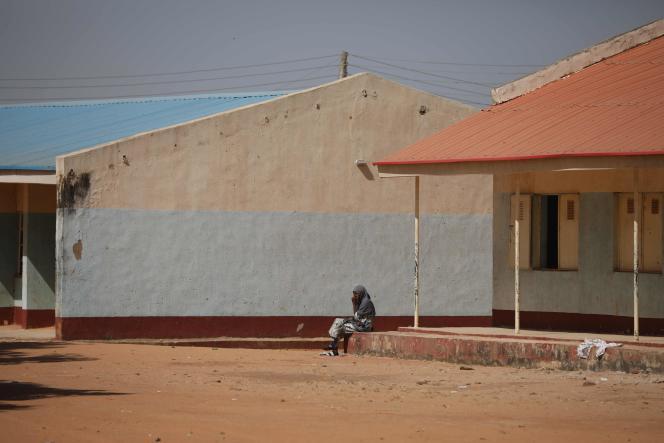 Un parent est assis à l'extérieur de l'école où des hommes armés ont enlevé des lycéens, le 15 décembre à Kankara, au Nigeria.