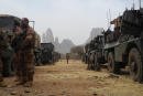 French soldiers stand by a convoy of armoured vehicles on March 27, 2019 with the Mount Hombori in the background during the start of the French Barkhane Force operation in Mali's Gourma region. - Troops will begin operating near the Burkina border from a new French military base in east-central Mali. The base will be the newest outpost of Operation Barkhane, France's 4,500-strong anti-jihadist force which is headquartered in Chad but also operates in Burkina Faso, Mali and Niger. (Photo by Daphné BENOIT / AFP)