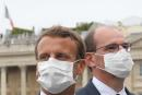 (FILES) In this file photo taken on July 14, 2020 French President Emmanuel Macron (C) and French Prime Minister Jean Castex both wearing a protective face mask react at the end of the annual Bastille Day military ceremony on the Place de la Concorde in Paris. French Prime Minister Jean Castex will self isolate after contact with President Emmanuel Macron who has tested positive for Covid-19, his office said on December 17, 2020. / AFP / POOL / Ludovic Marin