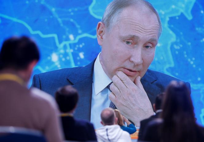 Des journalistes devant un écran qui diffuse la traditonnelle conférence de presse de fin d'année du président russe Vladimir Poutine, organisée en vidéoconférence, à Moscou, le 17 décembre.