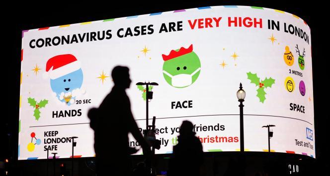 Des piétons passent devant un panneau d'information sur le Covid-19 avertissant que «le nombre de contaminations par le coronavirus est très élevé à Londres», à Piccadilly Circus, à Londres, le 19 décembre 2020.