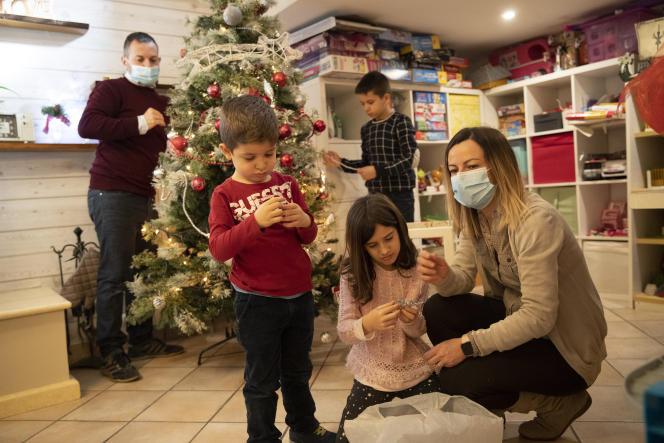 Une famille décore le sapin de Noël, dans leur maison de la banlieue de Rome, le 12décembre.