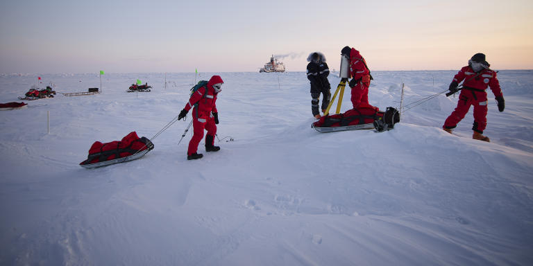Scientists on ice doing field work with Polarstern in the background
