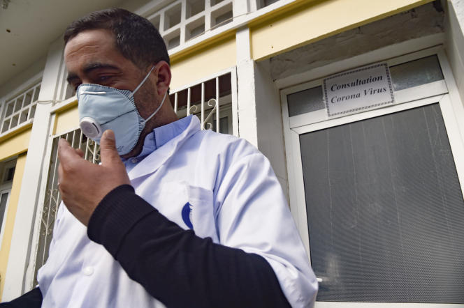 Un médecin algérien ajuste son masque à l'entrée d'un hôpital d'Alger, le 26février 2020.