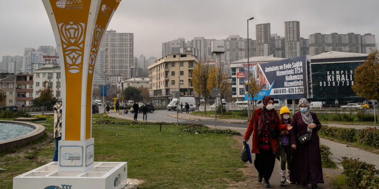 People walk through a park in an intersection of Esenyurt, a south western district of Istanbul, Turkey, on Thursday, December 3, 2020. In recent years, the working-class area of Esenyurt has become a refuge for thousands of refugees, primarily fleeing the war in Syria, but is also where cheap properties have been bought by a range of foreigners, including Iranians.   Iranians make up the highest proportion of foreign buyers in the Turkish housing market, according to the Turkish Statistical Institute. In recent years, foreign buyers have been attracted to investing in Turkey as the threshold amount has been lowered to $250,000USD to purchase property and provide a fast track to Turkish citizenship. Purchases of property by Iranians, primarily in Istanbul, nearly doubled between 2019 and 2020. One area in Istanbul - Esenyurt - is seeing a rise in the numbers of Iranians buying apartments and approximately 25% of one apartment block is now Iranian-owned.