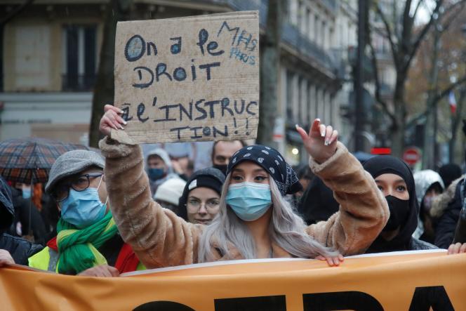 Une femme manifeste à Paris contre la loi« sécurité globale» et affiche sur sa pancarte son soutien à l'école MHS, le 12 décembre.