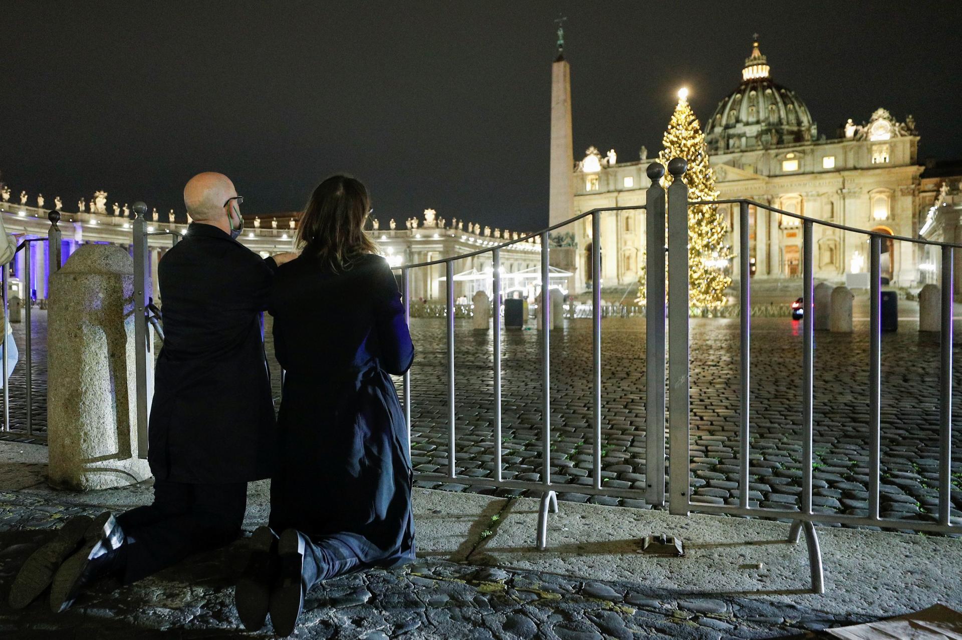 Des fidèles prient sur la place Saint-Pierre, à Rome, alors que le pape est en train de célébrer la messe de Noël dans la basilique, jeudi 24 décembre.