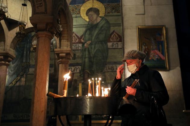 Un fidèle allume un cierge dans l'église du Saint-Sépulcre, à Jérusalem, jeudi24décembre.