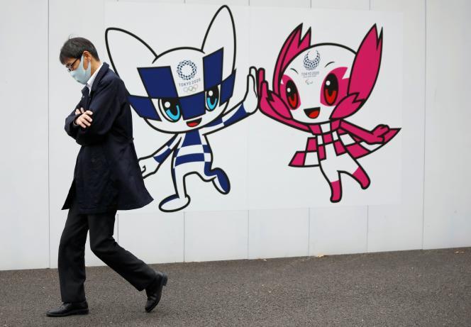 Un homme passe devant un mur décoré des mascottes de Tokyo 2020, à Tokyo, le24décembre 2020. Les organisateurs des JO ont prévu la création d'un centre de dépistage au village olympique pour des tests réguliers des athlètes, et l'installation de moyens de contrôle à l'entrée des sites. Le CIO réfléchirait à faire vacciner les athlètes avant l'événement.