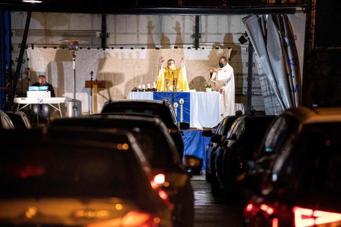 Un prêtre dirige une messe en plein air sur un autel de fortune installé dans un camion, la veille de Noël (2020), à Arlon, en Belgique. Les fidèles suivent la messe grâce à leur autoradio.