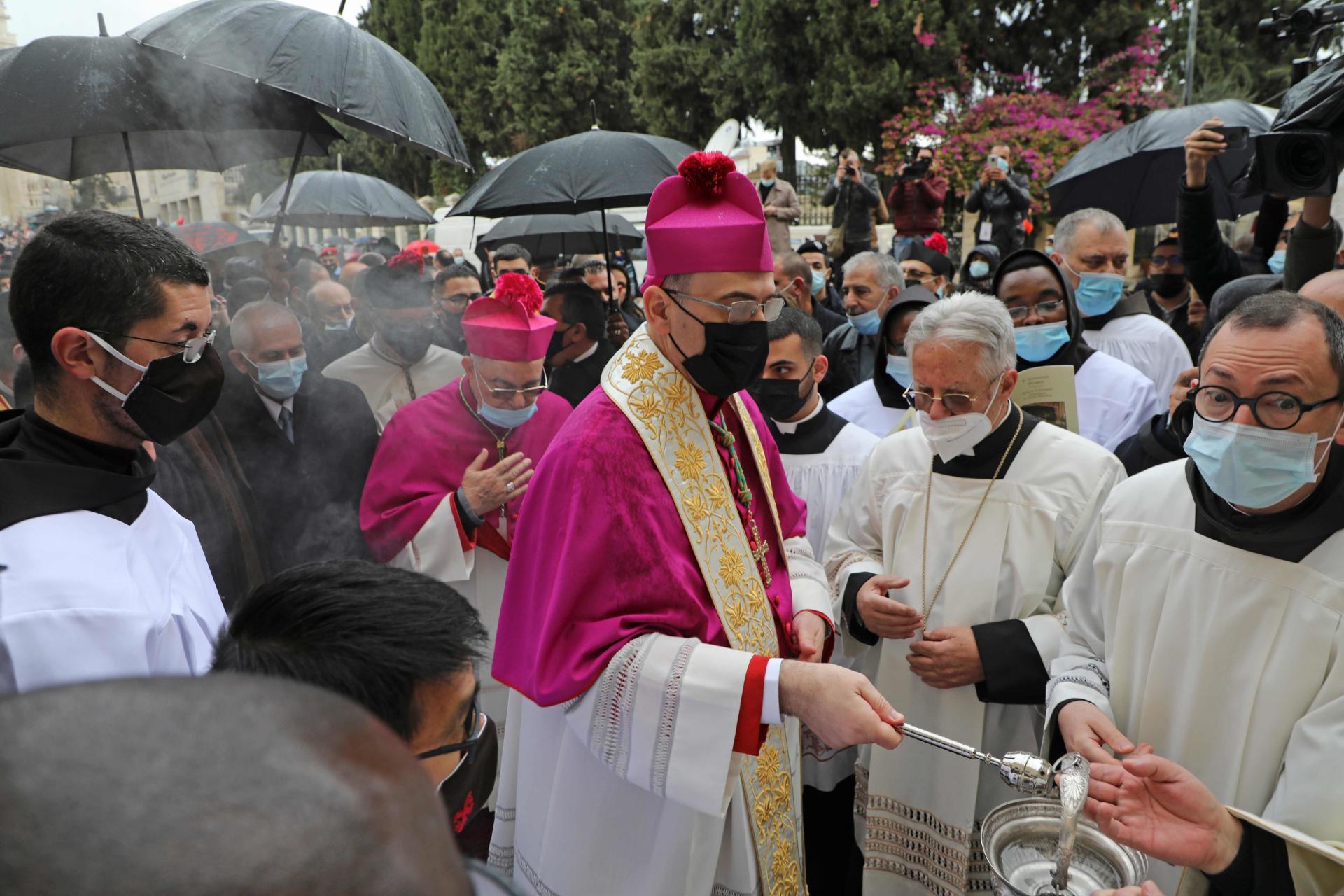 Le patriarche latin de Jérusalem, Pierbattista Pizzaballa, asperge la foule d'eau bénite lors de la procession à Bethléem, jeudi 24 décembre.