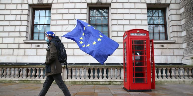A man wearing an EU flag-themed beret and carrying an EU flag is seen on Whitehall in central London on December 11, 2020. Prime Minister Boris Johnson on December 10 vowed to go the