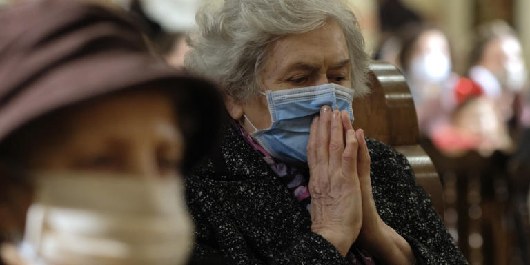 People wearing masks for protection against COVID-19 attend a Christmas Eve Mass at the Sacred Heart Cathedral in the capital Sarajevo, Bosnia, Thursday, Dec. 24, 2020. (AP Photo/Kemal Softic)