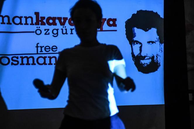 در این پرونده ، که در تاریخ 31 اکتبر 2018 ساخته شده است ، یک شرکت کننده در کنفرانسی مطبوعاتی که توسط وکلای وی در استانبول برگزار شد ، از صفحه ای که یک تاجر و نیکوکار زندانی عثمان کاوالا را نشان می دهد عبور می کند.  29 دسامبر 2020