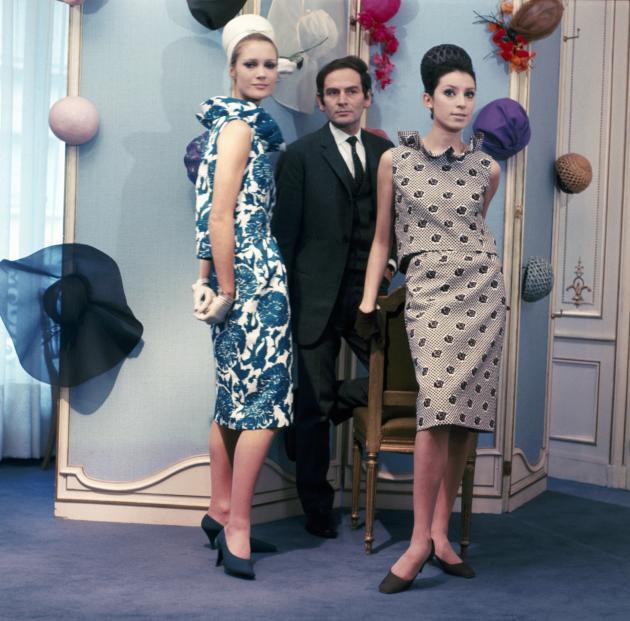Pierre Cardin avec deux modèles de sa maison de couture, dans les années 1960.