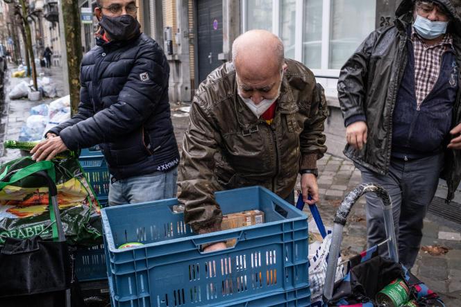 Un bénéficiaire de l'aide alimentaire range ses aliments dans son cadis et sacs, à Bruxelles, le 23 décembre 2020.