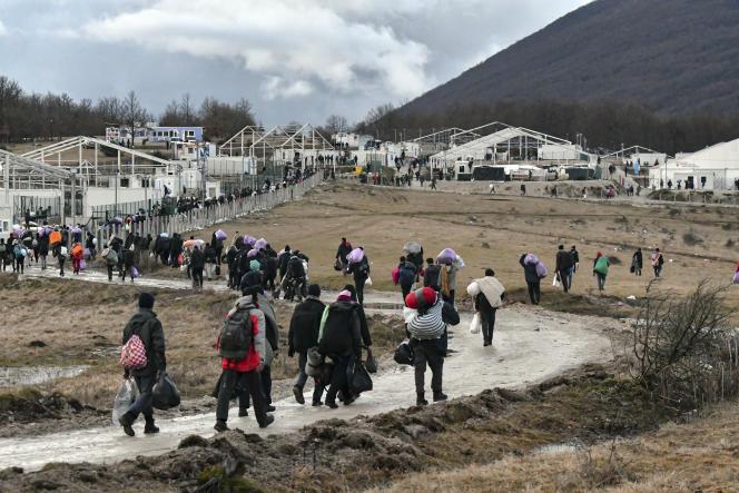 Des migrants retournent à pied au camp incendié de Lipa, près de Bihac (Bosnie), mercredi 30 décembre 2020. Des centaines d'entre eux devaient être transférés mardi vers un nouveau site dans le centre du pays, mais ils ont passé vingt-quatre heures dans des bus avant de se voir ordonner de retourner au camp, désormais vide.