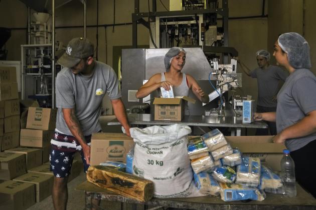 Dans les bâtiments dévolus au stockage, au traitement et à l'emballage du riz, des membres du MST s'affairent, le 26 octobre 2020, à Nova Santa Rita (Brésil).
