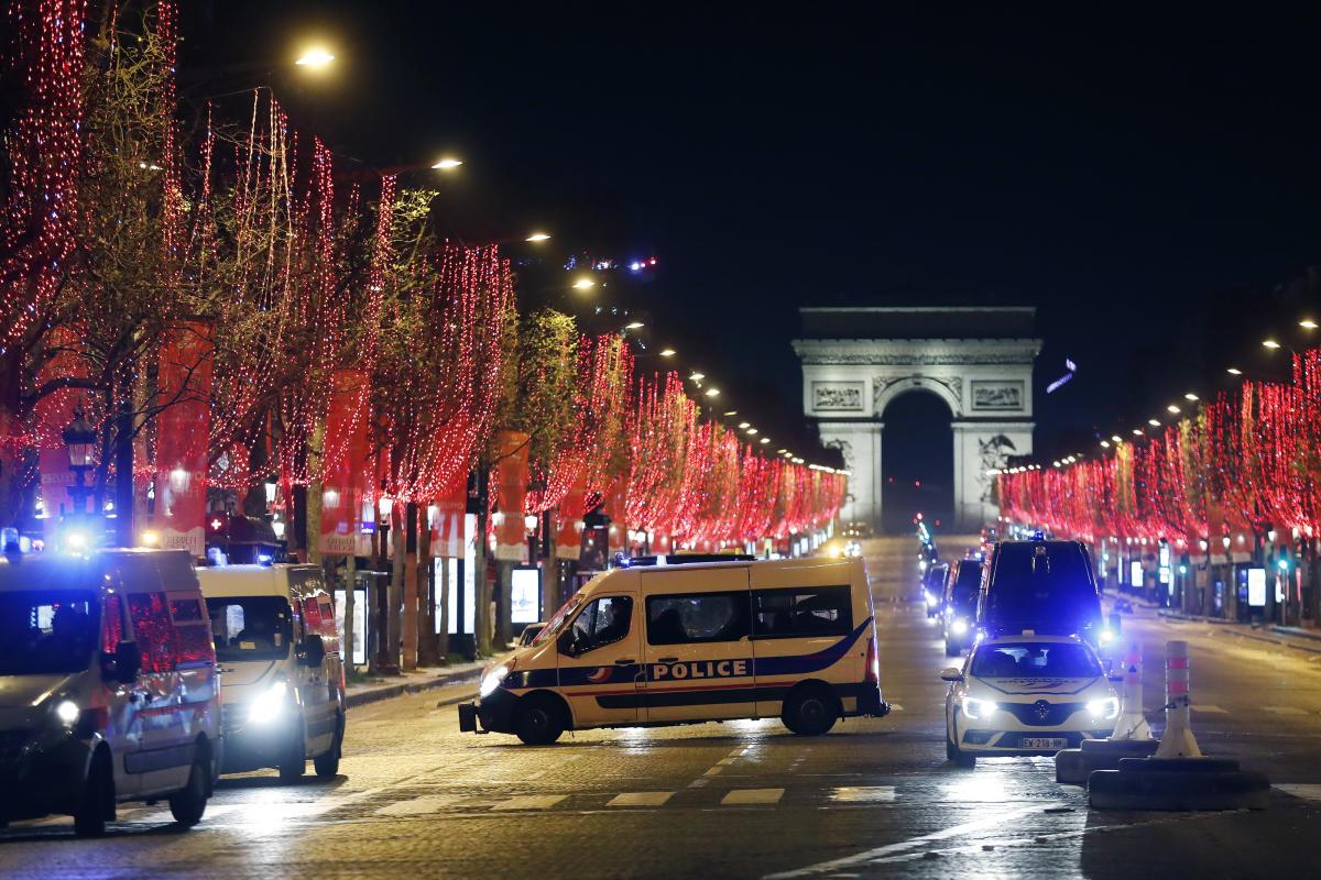 Des fourgons de police sont garés sur l'avenue des Champs-Elysées, à Paris, pendant le réveillon du Nouvel An.