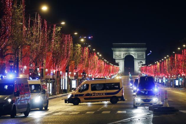 وانت های پلیس در شب سال نو در خیابان شانزه لیزه در پاریس پارک شده اند.
