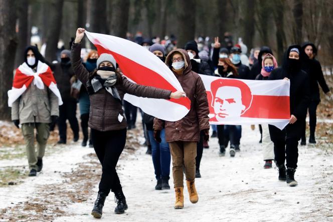 Des opposants au président Alexandre Loukachenko manifestent avec d'anciens drapeaux de la Biélorussie, à Minsk, le 13 décembre 2020.