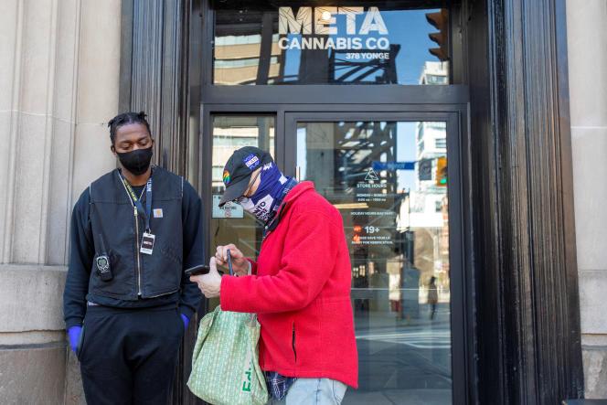 Un client commande du cannabis sur son téléphone devant le magasin Meta Cannabis, à Toronto, le 8 avril 2020.