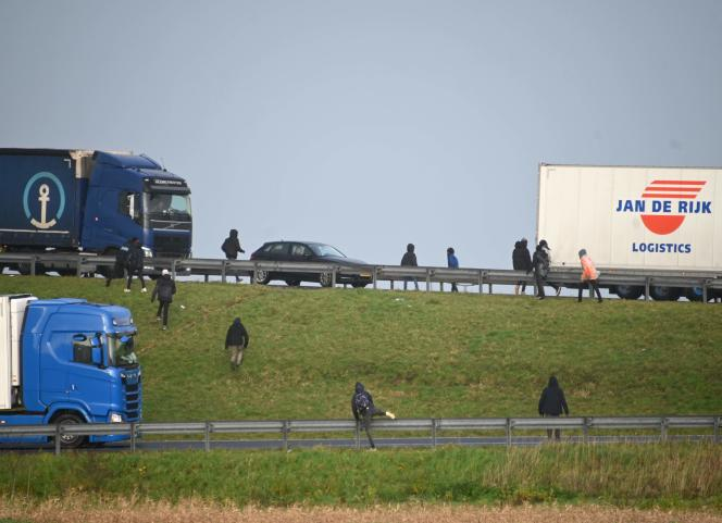 مهاجران در حال تلاش برای سوار شدن بر کامیون های پارک شده در ورودی تونل کانال در 17 دسامبر سال 2020 هستند.