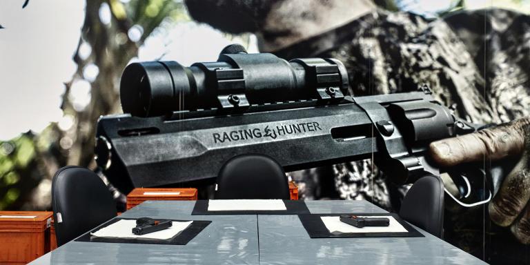"""Une salle de réunion dans les locaux de l'usine d'armement Taurus. Au mur, une affiche met à l'honneur le dernier revolver """"raging hunter"""" destiné à la chasse."""