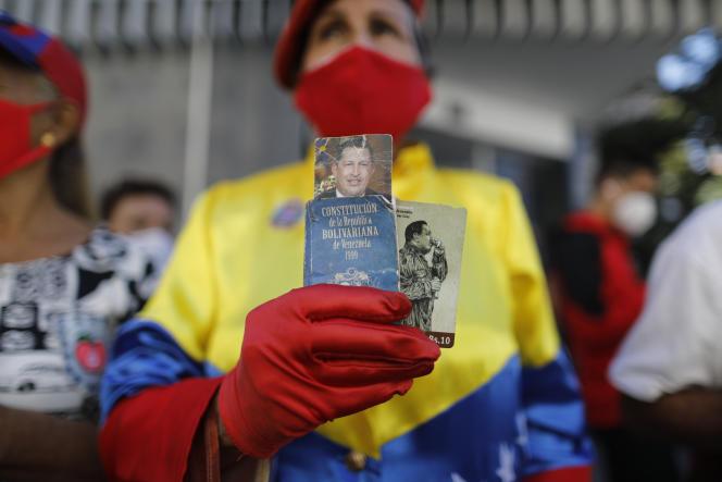Une femme tient la photo de Hugo Chavez et une petite version de la Constitution devant l'Assemblée nationale vénézuélienne, le 5 janvier.