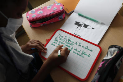 """A grils write during a class on freedom of expression and secularism, Monday Nov.2, 2020 in Strasbourg, eastern France. French schools reopened for the first time since the beheading of a teacher who opened a class debate on free speech by showing students caricatures of the prophet of Islam, in mourning and under tight security for a national homage. At schools throughout the country, students will read the letter of Jean Jaurès, a 19th century French thinker and politician, to instructors urging them to teach the country's children to """"know France, its geography and its history, its body and its soul."""" (AP Photo/Jean-Francois Badias)"""