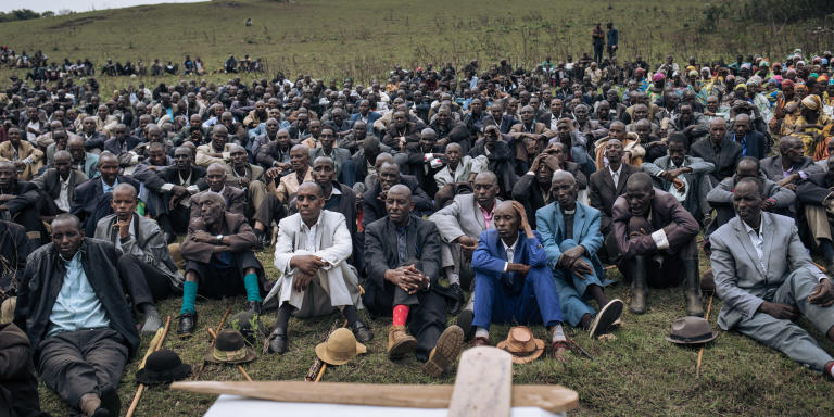 Men from the Banyamulenge community attend the funerals of a herder killed a day before by an armed militia, in a village near Minembwe, South Kivu province, eastern Democratic Republic of Congo, October 7, 2020. - Minembwe is an enclave inaccessible by land. The road going up from Uvira and Fizi on the shores of Lake Tanganyika is impassable. Apart from UN helicopters, a small carrier plane from Bukavu lands two or three times a week on the improvised airfield in the middle of the vast pastures at the foot of a mountain. (Photo by ALEXIS HUGUET / AFP)