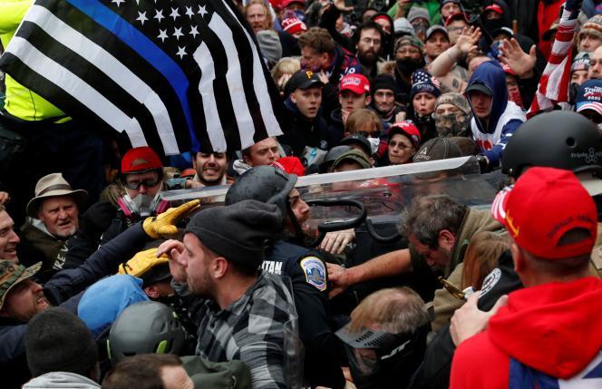 Sur cette photographie prise devant le Capitole, un agent des forces de l'ordre est débordé par les émeutiers.