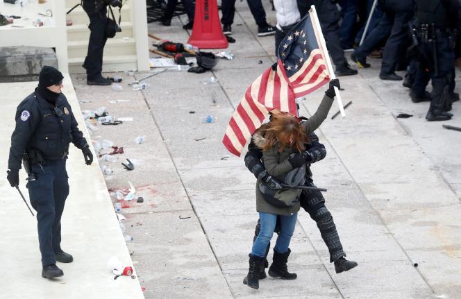 Une émeutière portant le drapeau de Betsy Ross est interpellée devant le Capitole.