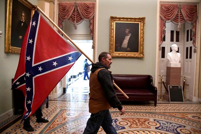 Un homme ayant pénétré de force dans le Capitole, à Washington, tient un drapeau confédéré.