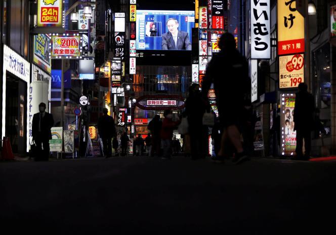 Un grand écran sur un bâtiment, à Tokyo, diffuse la retransmission en direct de la déclaration de l'état d'urgence par le premier ministre japonais, Yoshihide Suga, le 7janvier 2021.