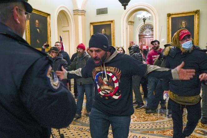 Un militant pro-Trump portant un tee-shirt du mouvement QAnon face à un policier, à l'entrée du Capitole, à Washington, le 6janvier.
