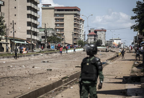 A Police officer looks on at protesters, as they continue to throw stones and block roads during mass protests after preliminary results were released in Conakry on October 23, 2020. - Guinea, gripped by days of post-election violence, suffered widespread internet disruptions on October 23, 2020, after preliminary results showed a victory for President Alpha Conde. (Photo by JOHN WESSELS / AFP)
