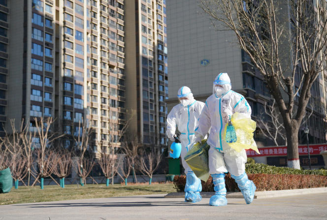 Photo by Chinese news agency Xinhua showing workers carrying Covid-19 test containers January 8 in Hebei province.
