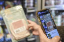 A person scans a product using the Yuka food and cosmetic scanner mobile phone application on November 25, 2020 in Paris. - The app uses product label to rate them by analysing their nutritional quality, presence of additives and organic aspect. (Photo by ALAIN JOCARD / AFP)