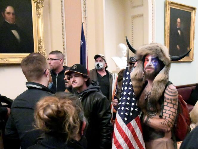 A droite sur la photo, Jacob Anthony Chansley, alias Jake Angeli.Complotiste torse nu, coiffé de cornes de bison et peinturluré, qui avait aimanté photographes et caméras aux quatre coins du Capitole, il a été arrêté et inculpé d'intrusion illégale et de conduite violente au Capitole, a annoncé le ministère de la justice américain dans un communiqué.